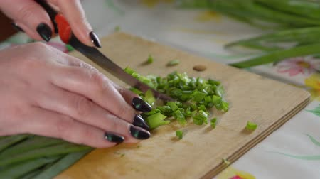 picado : Woman chopping green onions on a wooden cutting board.