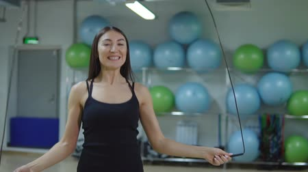 skákání : Fitness concept. Young woman jumping rope in the gym, slow motion