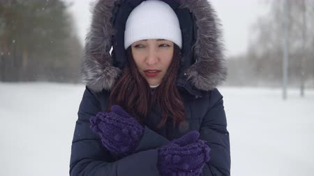 иней : Pretty girl in a white hat frozen for a walk in the winter. Стоковые видеозаписи