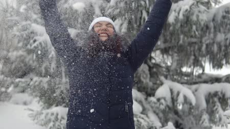 иней : Happy girl throw up snow in winter forest, slow motion