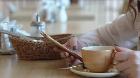 переписка : Young woman with a phone in a cafe. Close-up.