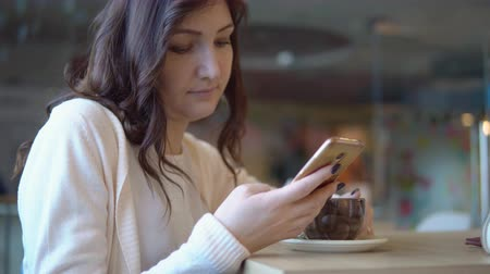 alkalmazottak : Beautiful brunette woman with phone drinks coffee.
