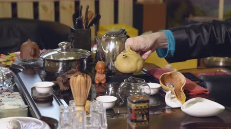 utensílio : Chinese traditions. Master pours tea from a glass teapot.