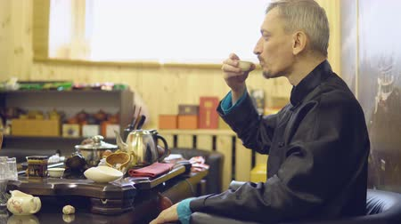 vanity : Tea ceremony. Master man drinking tea from a white mug.
