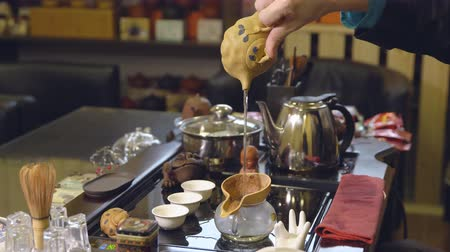 mistr : Master pours tea leaves with water. Tea ceremony.