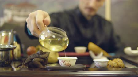 мастер : Master man pours green tea from a glass teapot into a white mug.