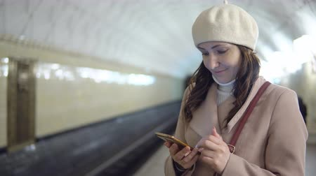 прибытие : Beautiful woman with a phone in the subway waiting for the train.
