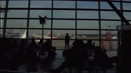 lobi : Airport waiting room overlooking the airplanes and clear sky.