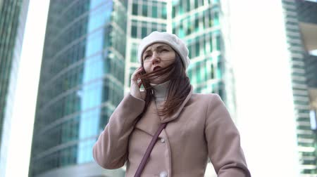 new town : Young woman talking on the phone among tall buildings.