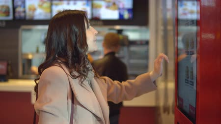 conveniente : Beautiful brunette woman in coat orders food through terminal.