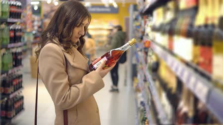 selecionando : Beautiful woman chooses pink wine in a supermarket department.