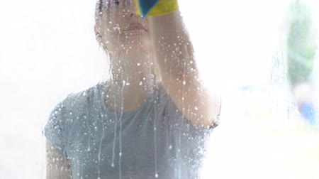 sprayer : Woman in yellow gloves washes the window with a detergent. Stock Footage