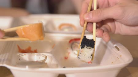 seafood dishes : Food delivery. Close-up of rolls in wooden sticks.