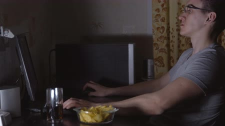 life energy : Young man is sitting at the computer and eating chips.