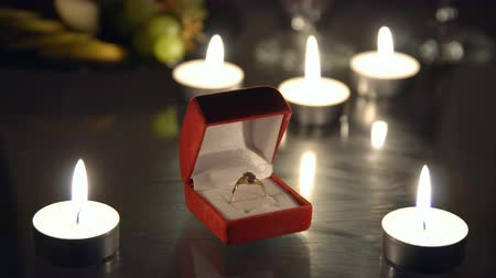 samet : Close-up of a ring in a red box against a background of burning candles.