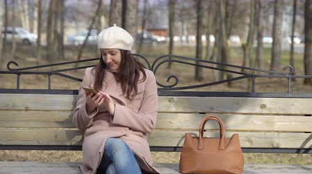 soymak : Woman sitting on bench with phone and robber with her purse.