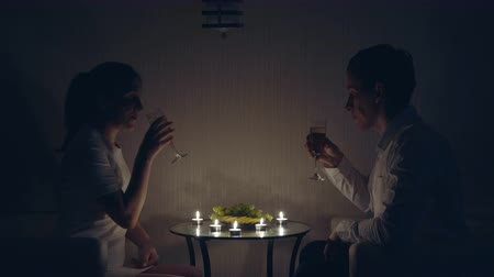 интимный : Romantic evening by candlelight. A man and a woman are drinking champagne.