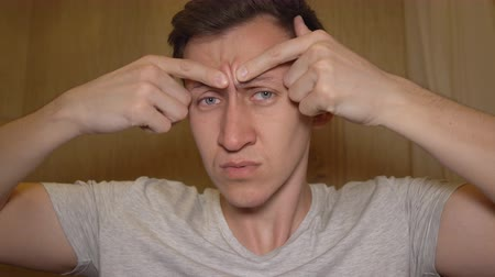 výrazy : Young man tries to squeeze out a pimple on his face. Dostupné videozáznamy