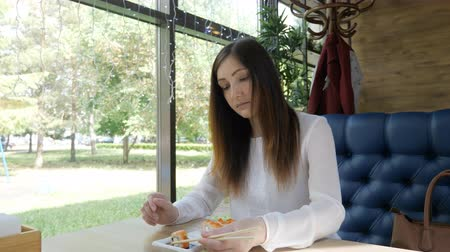 sushi roll : young woman in a cafe eats rolls with wooden sticks. Stock Footage