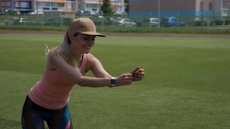 feliz : Young girl doing fitness exercise at the stadium outdoors. Healthy, sport and fitness concept, 4k