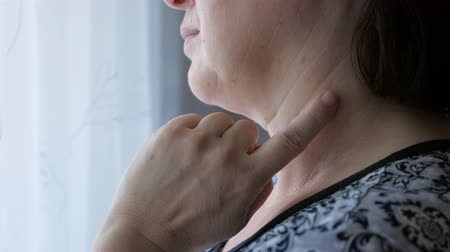 čtyřicet : close up of woman touching a mole on her neck.