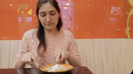 trigo sarraceno : Pretty girl eats a pancake with ice cream in cafe, close up. Vídeos