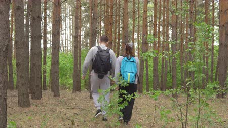 expedice : Man and woman walking through the forest holding hands.