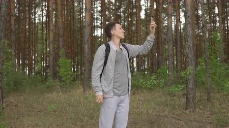 sem problemas : young man in the forest trying to catch a mobile signal.