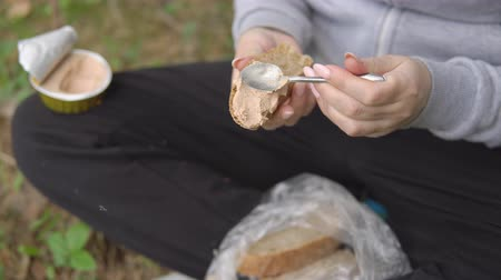 pasztet : young woman spreads pate on a piece of bread. Snack in the hike. Wideo