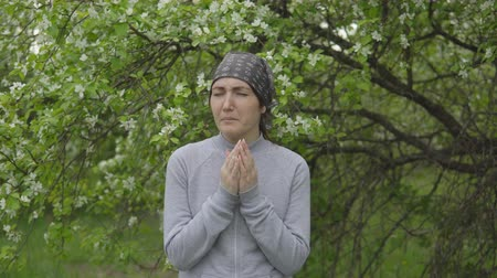 allergen : Young woman sneezes near an apple tree, an allergy. Stock Footage