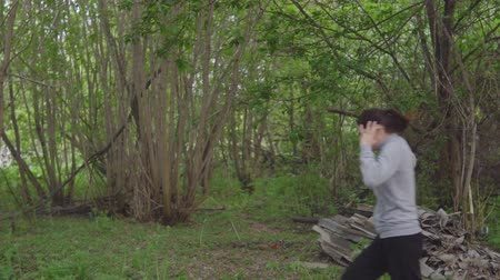 fejsze : man with an ax running after a young woman in the woods, slowmotion Stock mozgókép