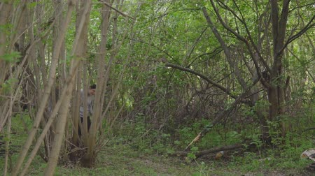 maniac : young woman in the forest runs away from a man with an ax, slowmotion