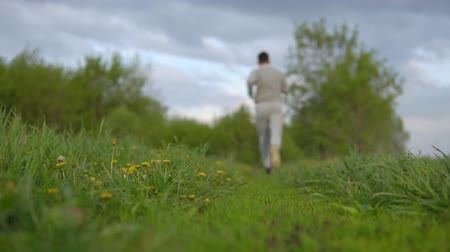 recreational park : Healthy lifestyle. A man is running around in the countryside, slowmotion