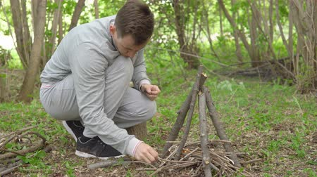 кемпинг : young man is lighting a fire in the forest.