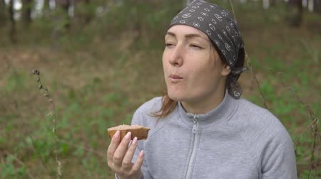 pasztet : Snack in the hike. Young woman eating a sandwich in the forest.