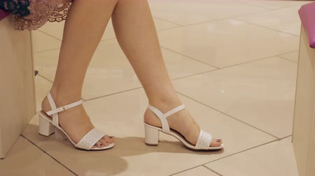 sandals : woman in a shoes shop is measuring white sandals.