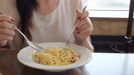 grated : young woman eating pasta with bacon in a cafe. Stock Footage