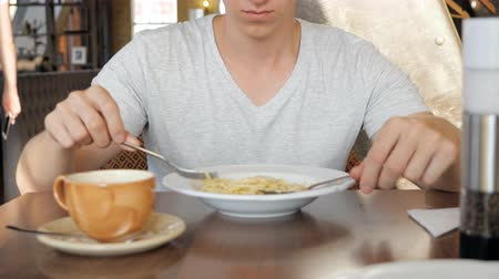 сделанный со вкусом : slow motion of young man in a cafe with an appetite eating a paste. Стоковые видеозаписи