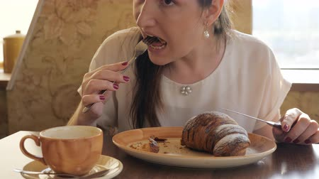 croissants : Young woman eats croissant and sings coffee at cafe.