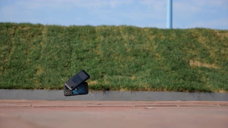 crashed : fall of a black phone on a pavement on the street, slow motion