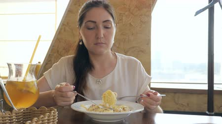harmful : Young beautiful woman in a cafe eating a pasta. Stock Footage