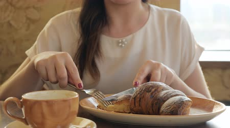 croissants : slow motion of young woman eats croissant and sings coffee at cafe. Stock Footage