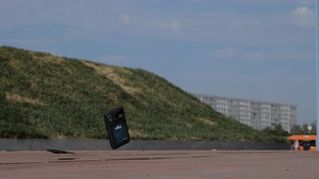 arranhão : Black touch phone fell to the sidewalk, slowmotion