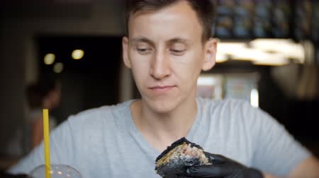 to bite : Hungry man in black gloves eating a burger in a cafe and drinks juice, slow motion