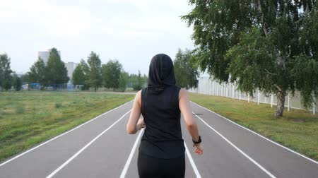 pista de corridas : Back view of fit girl runner running at the stadium outdoor, slow motion Stock Footage