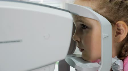 optyk : Optometrist examines the sight the little girl. Wideo