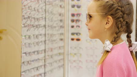 uv : Little cute girl trying on sunglasses at the store. Stock Footage