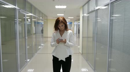 redhead suit : Businesswoman in suit walking and mobile phone in her hands in corridor of office.