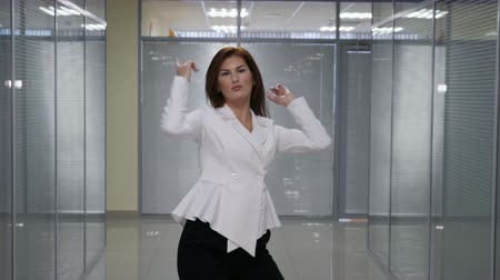 redhead suit : happy young businesswoman celebrating something on office background, slow motion Stock Footage
