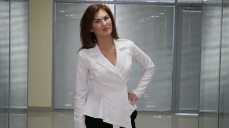 redhead suit : Beautiful smiling business woman standing against office background. Thumb up. Stock Footage
